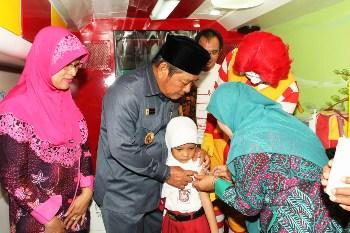 Bupati Saiful Ilah memegangi siswi yang diberikan imunisasi. [achmad suprayogi/bhirawa]