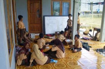 Puluhan siswa SDN Tobai Timur  4, terpaksa belajar di teras rumah warga. [F.nurkholis/ bhirawa]